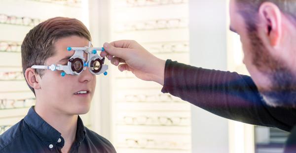 Optiker beim einstellen einer Testbrille an Kunden